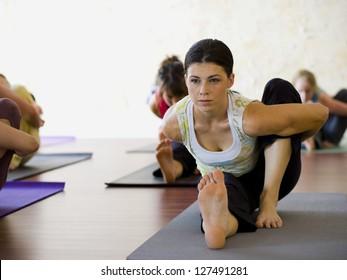 Women at yoga class stretching