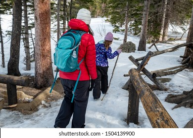 Women and young girl trek on a snow covered forest path through a woodland with during winter  Rocky Mountain National Park, CO