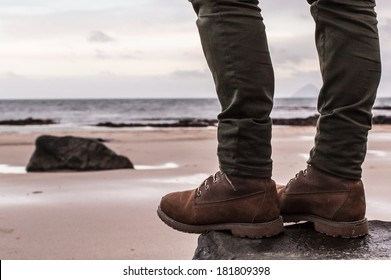 Women's 6-Inch Brown Waterproof Boots and skinny trousers on a rock with sand beach and ocean in the background. Scotland (UK)