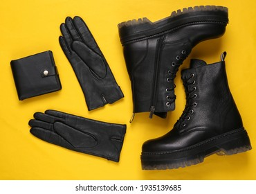 Women's accessories. Black Leather boots, gloves and wallet on yellow background. Top view. Flat lay