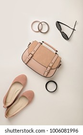 Women's accessories - gently pink, flesh-colored - shoes, bag and sunglasses. Selective focus.