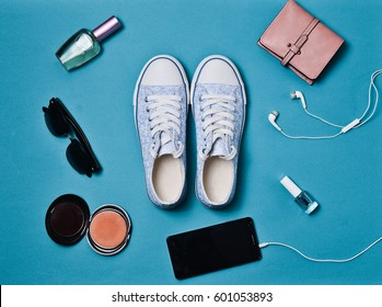 Women's accessories laid out on the blue surface. Snickers shoes, wallet, cosmetics, smartphone, headphones. Flat lay. Top view.