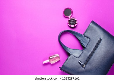 Women's accessories. Leather bag, perfume bottle, comb-mirror on pink paper background. Top view. Copy space