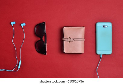 Women's accessories are lined on a red background. Smartphone, headphones, wallet, sunglasses. Flat lay.