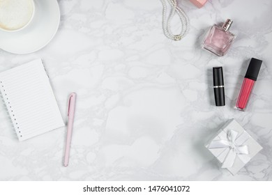 Women's accessories on a white marble table. Pink pen, notebook, perfume, gift box, pearls, a glass of coffee and other women's cosmetics. Layout for adding tags. Top view, flat lay, copy space