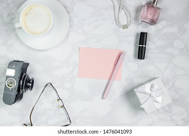 Women's accessories on a white marble table. A pink sheet of paper, pen, notebook, perfume, gift box, pearls, glasses, a glass of coffee and other women's accessories. Layout for adding tags. Flat lay