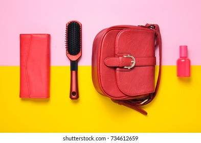 Women's accessories are red. Trendy products for girls on a pink yellow pastel background. Trend of minimalism. Hairbrush, purse, bag, perfume. Top view.