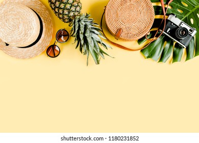 Women's accessories traveler: bamboo bag, straw hat, tropical palm leaves monstera, retro camera on yellow background. The concept of travel. Summer background. Flat lay, top view