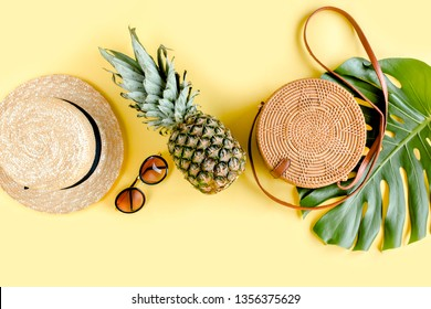 Women's accessories traveler: bamboo bag, straw hat, tropical palm leaves monstera on yellow background. The concept of travel. Summer background. Flat lay, top view