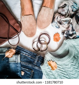 Women's autumn clothing set - jeans, suede sneakers, pullover, scarf and leather bag. Women's feet in suede sneakers surrounded by clothes for autumn walks on a light background, top view. Flat lay