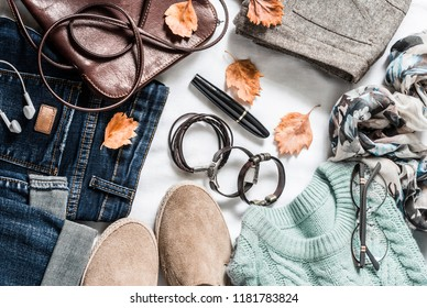 Women's autumn outfit set of clothes and accessories - pullover, jeans, suede sneakers, skirt, leather bag with light background, top view. Casual clothing for walking. Copy space, flat lay