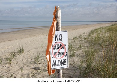 """Women's Bathing Suit Hanging From """"No Skinny Dipping Alone"""" Sign at Beach"""