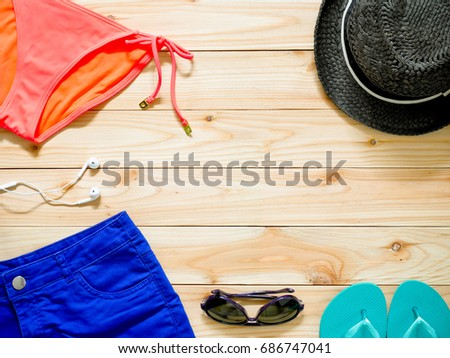 06b86a8329 Women's beachwear and accessories on wooden background. Beach clothing  concept.