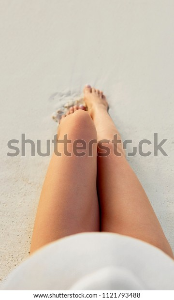 Women's Beautiful Sexy Legs on the Beach. Skin care and Protection Sun. Spa Concep. Epilation Laser or Shaving Concept. Sunscreen on Feet.