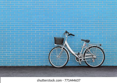 Women's bicycle against a turquoise brick wall