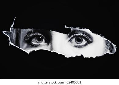 Women's bl eyes spying through a hole