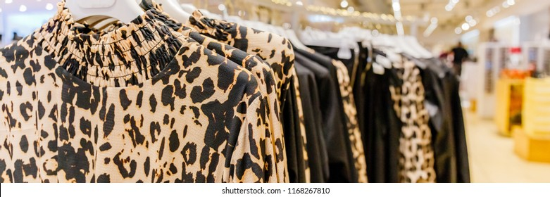 Women's blouses with classic animal print hang on hangers, banner background