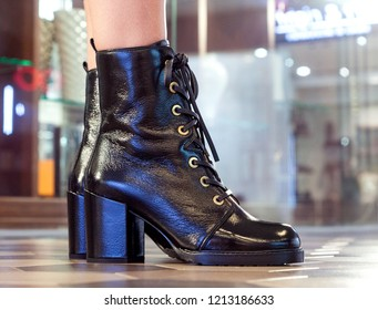 Women's boots. Ankle boots on slender female legs close-up.
