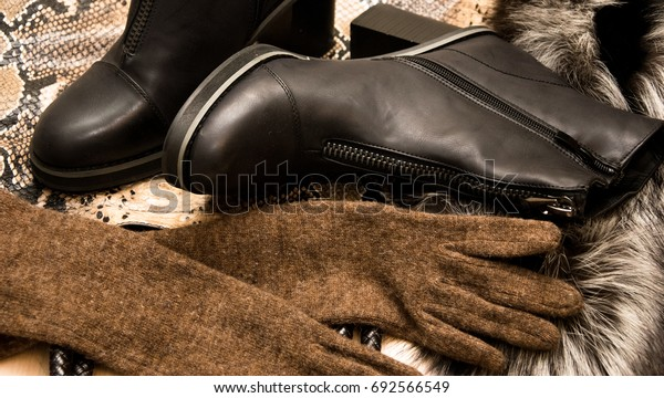 Women's boots, fur, gloves on the background of snake skin