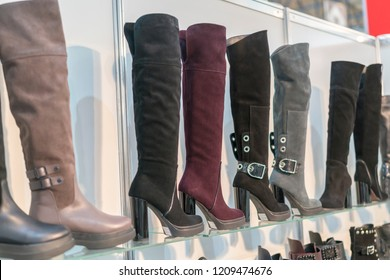 women's boots on the shelves in the store. Pavilion of the store with fashionable women's shoes. Leather autumn-winter boots.