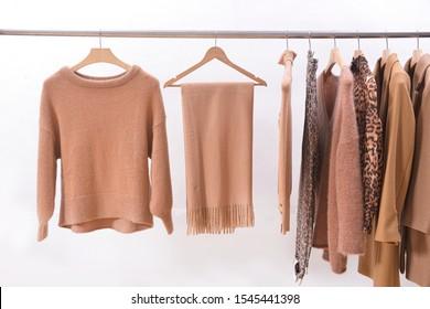 Women's brown blouses with, snake pattern coat,,pants scarf, jacket, sweater, handbag on hangers