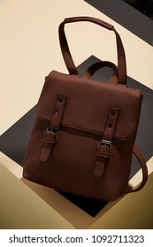 Women's brown leather backpack in vintage style, with a flap top, handle, straps and buckles, angle view. The fashionable accessory for office, business trips or casual occasions placed on a desk top.