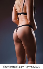 Women's the buttocks in black panties on a gray background