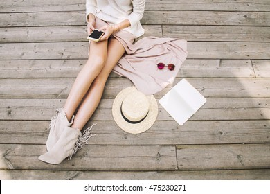 Women's casual accessories on wooden background: sunglasses, empty sketchbook, hat.Beautiful female legs in dusty pink skirt.Lifestyle and fashion concept.Mock up for text.Girl's hands with smartphone