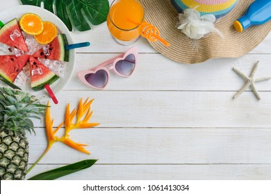Women's casual clothes with accessories items and tropical fruits and flowers on white wooden background, I love summer concept, Copy space