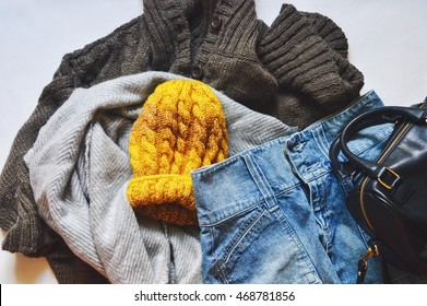 Women's clothes: a brown woolen cardigan, gray scarf, denim skirt and a yellow hat. Casual style. Autumn or winter outfit. Flat lay, top view photography