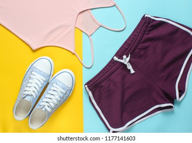 Women's clothing and accessories for fitness on a colored pastel background. Sneaker, sports shorts, T-shirt. Flat lay style. Top view