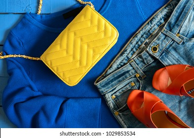Womens clothing, accessories, footwear (blue blouse, jeans, leather terracotta shoes, yellow crossbody bag). Fashion outfit. Shopping concept. View from above.  Trendy, saturated colors
