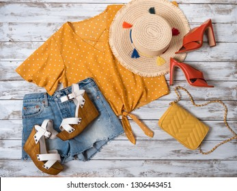 Womens clothing, accessories, footwear (heels shoes, wedges sandals, denim shorts, yellow blouse, crossbody bag, straw hat. Fashion outfit, spring summer collection. Shopping concept. Flat lay