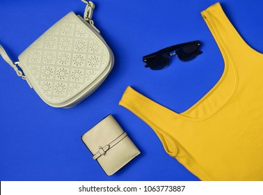 Women's clothing and accessories laid out on a blue background. yellow T-shirt, purse, bag, sunglasses. Top View. Flat lay.