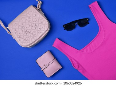Women's clothing and accessories laid out on a blue background. Purple T-shirt, purse, bag, sunglasses. Top View. Flat lay.