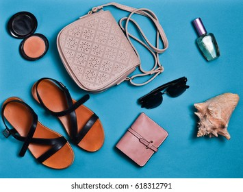 Women's clothing and accessories laid out on the blue surface. Sandals, bag, wallet, cosmetics, sunglasses. Flat lay. Top view.