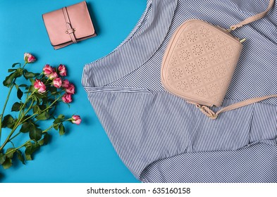 Women's clothing and accessories laid out on a blue background. Blouse, women's bag, purse, bouquet of roses. Top View. Flat lay.