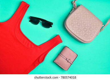 Women's clothing and accessories laid out on a turquoise background. Red T-shirt, purse, bag, sunglasses  Top View. Flat lay.