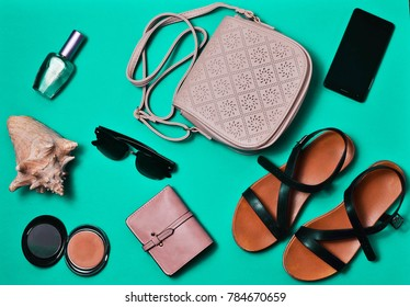 Women's clothing and accessories laid out on the blue surface. Sandals, bag, wallet, cosmetics, smartphone. Flat lay. Top view
