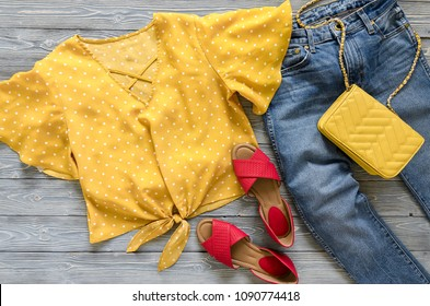 Womens clothing, accessories, shoes (yellow blouse in polka dot, blue jeans, leather red sandals,  yellow crossbody bag). Fashion outfit. Shopping concept. Flat lay. Trendy, saturated colors.