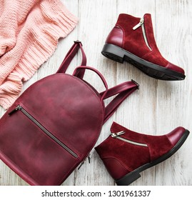 Womens clothing, backpack , boots on a old wooden table