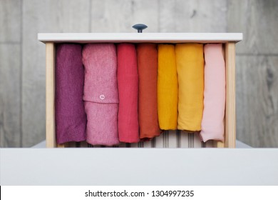 women's clothing, neatly folded in the closet, different bright spring shades