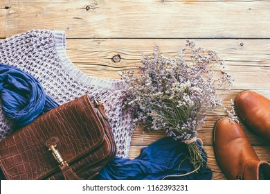 Women's clothing on a wooden background, red shoes bag and sweater