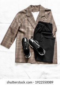 Women's clothing - plaid jacket, black trousers and leather sneakers shoes on a light background, top view