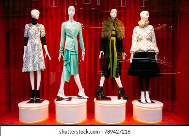 Women's clothing store. Mannequins dressed in stylish clothes behind shop-window, on red background.