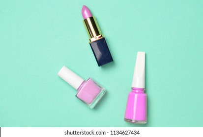 Women's cosmetics and accessories for beauty care on a blue pastel background. Nail polish, lipstick, top view, minimalist trend