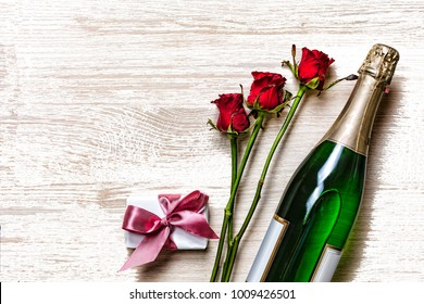 Women's Day, 8 March.  Valentine's Day. Valentine's Day. Champagne, gift box and red roses. Layout. Free space for text. Birthday, Wedding, Mother's Day, March 8