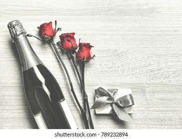 Women's Day, 8 March. Valentine's Day. Valentine's Day card. Champagne, gift box and red roses. Layout. Free space for text.
