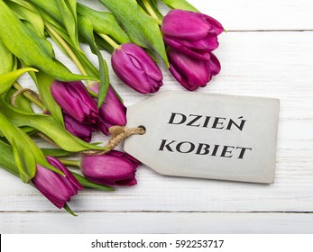 Women's day card with Polish words DZIE? KOBIET. Tulip flowers on white wooden background.
