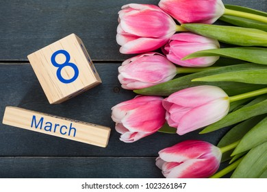 Women's day concept. Pink tulips bouquet and the March 8th date on blue wooden background